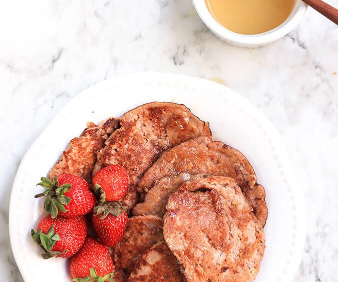 Nutty, textured low-carb pancakes made with ground walnuts, shredded coconut and Greek yogurt. Best with fresh strawberries and a drizzle of raw honey!